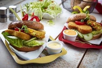 Auf dem Bild sind 2 Burger zu sehen, welche mit Gemüse Schnitzeln, Salat, Gurken und Tomaten belegt sind. Sie liegen auf einem Tablett, welches sich auf einem Holztisch befindet. Ebenfalls auf dem Tisch stehen Schalen mit Mayonnaise. Im Hintergrund ist eine Schale mit Salat, so wie Salz und Pfeffer zu erkennen.
