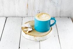 """Alpro® For Professionals. Auf dem Bild ist eine grüne Tasse zu sehen, in der ein Kokosnuss Cappuccin """"Latte Art"""" gefüllt ist. Die tasse steht auf einem runden stück Holz, auf dem zur Dekoration kokosnussstücke liegen."""