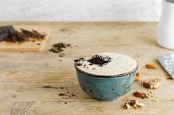 Alpro® For Professionals. Auf dem Bild ist in einer Antiken, grünen Tasse ein Mandel Cappuccino. Der Cappuccino ist mit geraspelter Schokolade bestreut. Im Hintergrund ist gehakte Schokolade zu sehen.