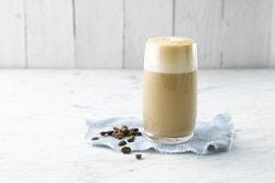 Alpro® For Professionals. Das Bild zeigt einen Soja latte Macchiato. Er ist auf ein tuch auf einem tisch platziert. Daneben liegen Kaffeebohnen zur Zierde.