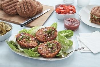 3 Buletten von DALOON bestehend aus Bohnen auf einem Teller mit Salat angerichtet. Im Hintergrund sind Burgerbrot sowie Tomaten und Ketchup zu sehen.