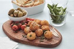 BestCon Cheese Bites von Daloon. Die Mac&Cheese Bites sind mit grünen Oliven und Cherrytomaten auf einem Holzbrett drapiert.