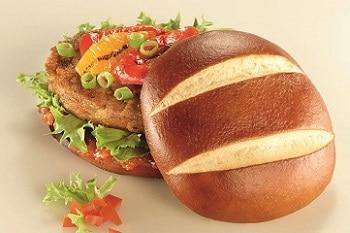 Auf dem Bild ist ein Burger zu erkennen, dessen Burger Brot aus Laugenbrot besteht. Der Burger ist mit Salat, Lauchzwiebeln und Ketchup belegt.