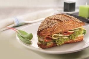 Ein Sandwich belegt mit Salami, Käse und Salat