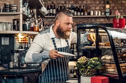 Auf dem Bild erkennt man einen Mitarbeiter eines Cafés, welcher mit der linken Hand einen Kuchen aus der Theke holt. In der rechten Hand hält er einen Teller. Im Hintergrund sind Regale zu sehen, auf welchen Getränke stehen. Die Theke ist mit Pflanzen geschmückt.