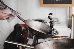 Auf dem Bild ist eine Pfanne zu sehen, in welcher Muscheln gekocht werden. Man sieht eine Hand, die die Pfanne mit einem Handtuch festhält.