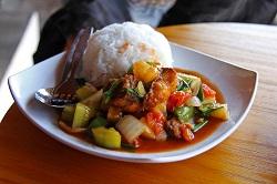 Auf dem weißen Teller ist ein süß sauer Gericht zu erkennen. Es befinden sich verschieden Gemüsesorten, sowie Reis auf dem Teller.