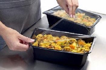 Asia Food In dem Bild ist das asiatische Gericht in einem schwarzen Container zu sehen. Während im Hintergrund eine Hälfte bereits fertig laminiert wurde, wird die im Fokus stehende Hälfte der beiden Container gerade von einer Arbeitskraft mit durchsischtiger Folie verschlossen.