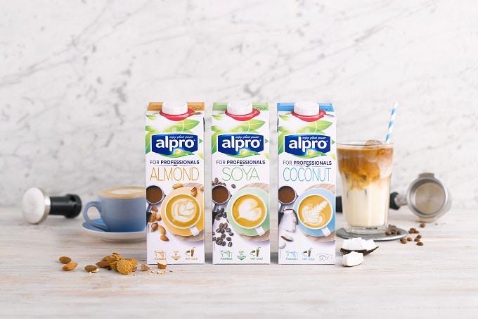 Auf dem Bild sind 3 Milchalternativen von Alpro for Professionals in Tetra Paks zu sehen. Dabei handelt es sich um Mandel-, Soja- und Kokosnussmilch. Neben den Tetra Paks sind ein Kaffee in einer Tasse und ein Milchshake in einem Glas zu sehen.