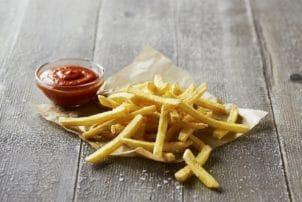 Die QuickOvenFries von Farm Frites auf einem hölzernen Hintergrund auf einer Papiertüte. Daneben eine Schale mit Ketchup.