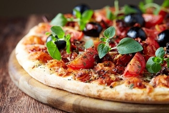 Eine Pizza mit Kirschtomaten, Oliven und Gewürzkräutern.