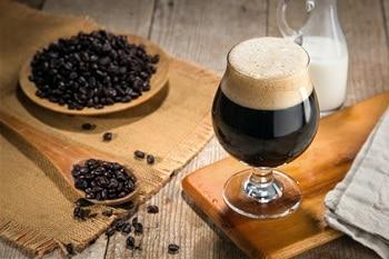 Auf dem Bild ist ein sogenannter Nitro Coffee in einem Glas zu sehen. Neben dem Kaffeeglas sind Kaffeebohnen auf einem Teller und einem Holzlöffel zu sehen. Im Hintergrund steht eine Kanne Milch.