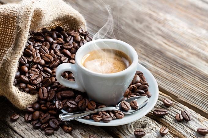 Auf dem Bild ist eine Tasse Kaffee zu sehen, welcher vor Hitze dampft. Die Tasse liegt auf einem Tassenteller, welcher sich auf einem Holztisch befindet. Neben der Tasse liegt ein Sack voll mit Kaffeebohnen, von welchen einige auf dem Teller und dem Tisch liegen.
