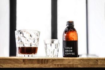 Auf dem Bild ist eine Theke abgebildet, auf welchem sich zwei Gläser und eine Flasche befinden. Ein Glas ist mit Cold Brew Coffee gefüllt, das andere Glas ist leer. Die Flasche ist ebenfalls mit Cold Brew Coffee gefüllt und mit einem Schriftzug beschriftet.