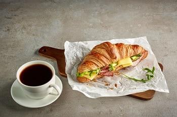 Auf dem Bild ist ein Croissant auf einem Holzbrett zu sehen. Das Croissant ist mit Käse, Schinken und Salat belegt. Neben dem Croissant steht eine Tasse Kaffe.