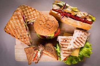 Hot Dog, Burger, Wraps und Sandwiches auf einer Holzplatte