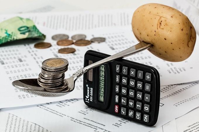 Auf dem Bild ist ein Taschenrechner zu erkennen, der einen Löffel ausbalanciert, auf dem auf der einen Seite eine Kartoffel und auf der anderen Seite mehrere Münzen liegen. Im Hintergrund sind Münzen und ein Geldschein zu sehen, die auf Zetteln liegen.