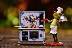 Auf dem Bild ist eine Froschfigur, die als Kellner angezogen ist, zu sehen. Neben der Figur steht ein Herd in Miniaturform. Auf dem Herd befindet sich eine Pfanne, sowie ein Topf.