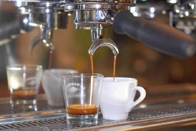 Eine Tasse und ein Glas in die Kaffee von Grean and Bean gefüllt wird
