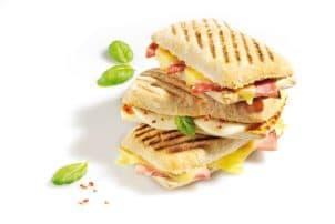 Drei Sandwiches aufeinander belegt mit Salami, Schinken, Käse und Ei.