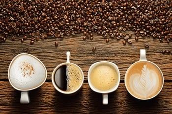 Auf dem Bild sind vier Tassen unterschiedlicher Kaffe zu sehen. Neben dem Kaffee sind zahlreiche Kaffeebohnen.