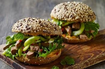 Auf dem Bild sind zwei Burger zu sehen. Die Burger Brötchen bestehen aus Vollkorn. Belegt sind sie unter anderem mit Salatblättern und Gurken.