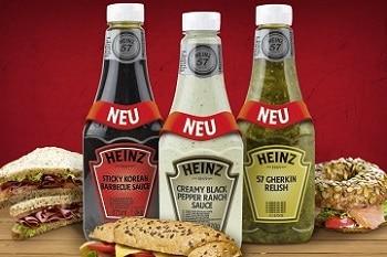 Auf dem Bild sind 3 Snack Saucen von Heinz zu sehen. Die linke Sauce ist eine Barbecue Sauce in einer schwarzen Flasche. Die mittlere Flasche ist weiß und beinhaltet eine creamy black pepper ranch Sauce. Die rechte Flasche ist grün und beinhaltet ein Relish. Neben den Saucen sind zwei Sandwiches und ein Bagel abgebildet.