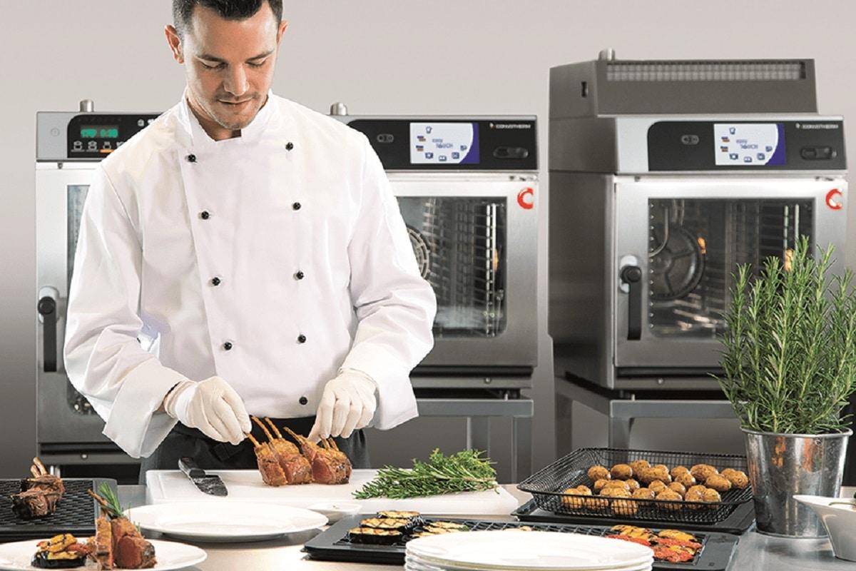 Auf dem Bild ist ein Koch zu erkennen, welcher Snackgerichte auf Tellern anrichtet. Im Hintergrund sind 3 verschiedene Modelle des Convotherm minis des Herstellers Welbilt zu sehen.