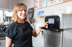 Auf dem Foto ist der Merrychef eikon e2 des Snackgeräte-Herstellers Welbilt zu sehen. Das Küchengerät wird von einer Café-Mitarbeiterin, die eine schwarze Schürze trägt, mit der linken Hand bedient. Die Mitarbeiterin ist von vorne zu erkennen.