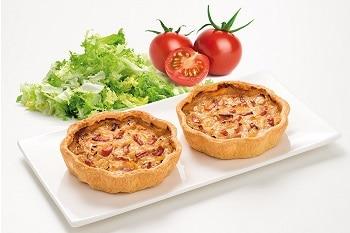 Zwei Quiches auf einem Teller, gefüllt mit Käse und Schinken. Neben dem Teller sind Tomaten und Salat zu sehen.
