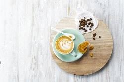 """Alpro® For Professionals. AUf dem Bild ist ein kleiner Cappuccino """"Latte Art"""" zu sehen, welcher von oben abfotografiert wurde. Er ist in einer pastell grünen Tasse mit Untertasse. Auf der Untertasse liegt ein Keksgebäck. Neben dem Teller sind auf einem Holzbrett Kaffeebohnen verteilt."""