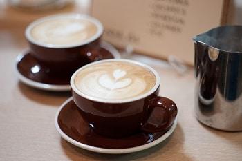 Auf dem Bild sind zwei Tassen Kaffee nach Latte Art zu sehen. Neben den Tassen steht eine Kanne Kaffee.