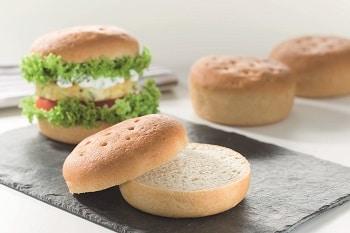 Auf dem Bild sind glutenfreie Burger Brötchen zu sehen. Im Vordergrund liegen 2 Brötchen aufeinander. Dahinter ist ein mit Salat, Tomaten, Remoulade und vegetarischer Bulette belegter Burger zu sehen. Im Hintergrund sind 2 weitere glutenfreie Burger Brötchen.