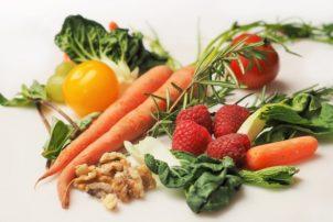 Auf dem Bild sind Karotten, Himbeeren, Weintrauben und Salatblätter zu sehen.