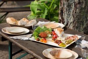 Auf dem Bild sind mehrere Teller aus Palmblatt zu sehen, auf denen sich Salate, Garnelen und Fleisch befinden.