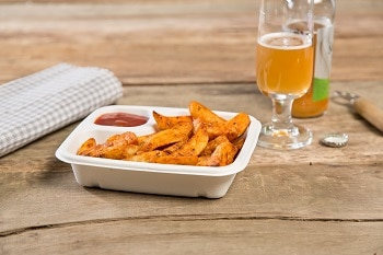 Eine Schale aus Zuckerrohr, in der sich Pommes und Ketchup befinden. Im Hintergrund sind ein Glas und eine Flasche mit Bier.