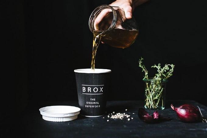 Hühnerbrühe von Brox, die in eine Becher gefüllt wird.