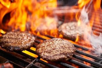 Auf dem Bild sind Burger Patties zu sehen, die auf einem flammenden Grill gegrillt werden.