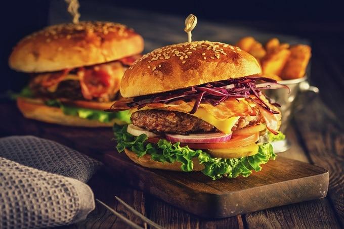 Auf dem Bild sind zwei Burger zu sehen, die sich auf einer Holzplatte auf einem Holztisch befinden. Der Burger ist mit einer Bulette, Käse, Speck, Gurken, Zwiebeln, Tomaten und Salatblättern belegt. Im Hintergrund ist eine Schale mit Pommes zu erkennen.