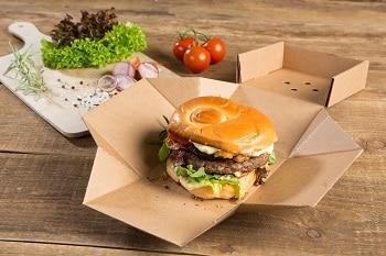 Auf dem Bild ist ein Burger, belegt mit einer Bulette, Zwiebeln, Salatblättern, Käse, Speck, und Tomaten, zu sehen, der in einer Kartonverpackung liegt. Im Hintergrund ist eine weitere Kartonverpackung zu sehen sowie Tomaten und ein Holzbrett, auf welchem Salatblätter und Zwiebeln liegen.