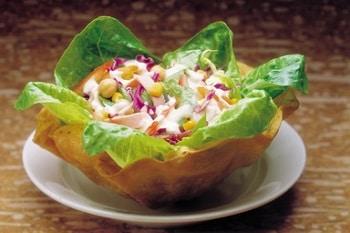 Auf dem Bild ist ein Salat innerhalb einer essbaren Waffelschale zu sehen.
