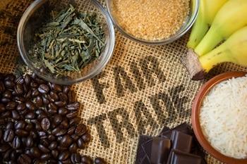Auf dem Bild ist ein Schriftzug Fair Trade zu sehen. Um den Schriftzug liegen Bananen, eine Schale Reis, Schokolade und Kaffeebohnen.