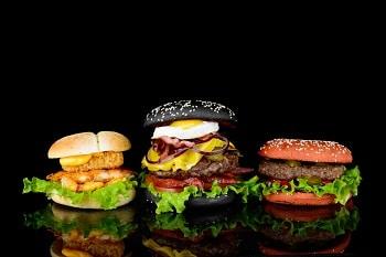 Auf dem Bild erkennt man farbige Burger vor einem schwarzen Hintergrund. Der rechte Burger hat rote Burgerbrötchen, ist mit einer Bulette, einem Salatblatt und Tomaten belegt. Der Burger in der Mitte hat schwarzes Burgerbrot und ist mit Ei, Speck, Käse, Zwiebeln, Tomaten und Salat belegt. Der linke Burger hat normales Burgerbrot und ist mit Hühnchen und Salat belegt.