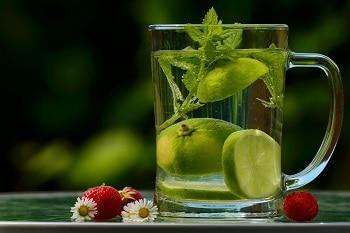 Eine hausgemachte Limonade in einem Glas, in welchem sich ebenfalls Limettenscheiben befinden. Neben dem Glas liegen drei Erdbeeren und drei Gänseblümchen.