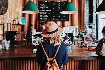 Auf dem Bild ist eine Kaffeebar abgebildet. Das Personal steht hinter einer Theke und bedient gerade Kunden, wie eine Frau mit Hut und Tasche auf dem Rücken. Im Hintergrund ist eine Tafel an der Wand zu sehen, auf welchem das Angebot, so wie die dazugehörigen Preise zu finden sind.