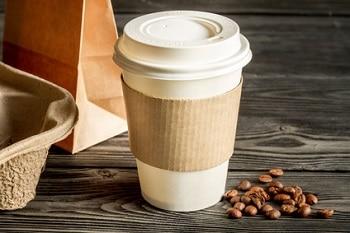 Ein to go Kaffeebecher auf einem dunklen Holzhintergrund. Neben dem Becher sind Kaffeebohnen zu sehen.