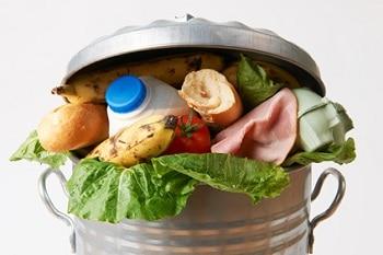 Eine Mülltonne, in der sich frische Lebensmittel, wie Schinken, Brot, Bananen und Milch befinden. Das Bild illustriert Lebensmittelverschwendung.