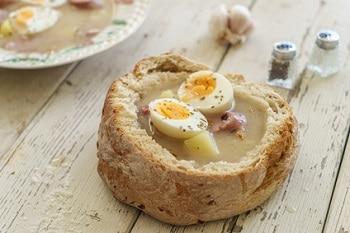 Ein Brot, welches als Bowl dient und in der Mitte ausgehüllt ist. Im Brot befindet sich eine Zurek Suppe mit Eiern und Würstchen.