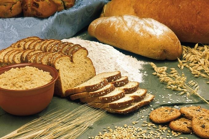 Auf dem Bild sind verschiedene Sorten von Broten sowie Getreide und Mehl zu sehen.