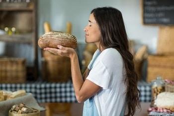 Eine Frau mit weißen T-Shirt und Schürze um, die ein Laib Brot in den Händen hält und mit geschlossenen Augen daran riecht.